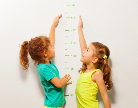 벽에 서서 규모에 손을 뻗어 높은 점수에 도달하려는 두 어린 소녀