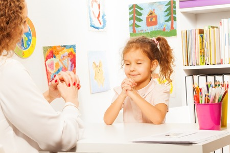 child sitting: Schoolgirl closes her eyes and exercises putting fingers with teacher at the desk Stock Photo