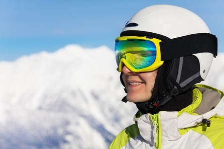 ski mask: Close-up profile portrait of a smiling woman wearing ski mask and helmet over mountains