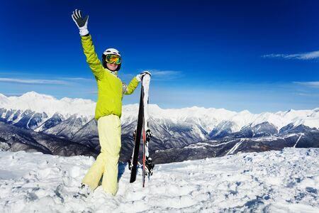full height: Full height portrait of woman with ski looking ant mountains waiving hands and looking back