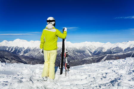 full height: Back full height portrait of the woman skier with helmet and mask looking over valley and high mountains Stock Photo