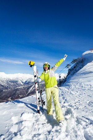 full height: Full height portrait of a woman taking selfie over the mountain in ski outfit Stock Photo