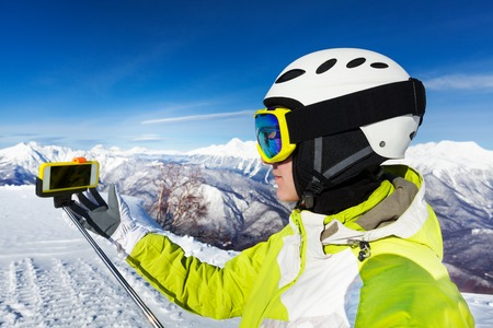 ski mask: Portrait of woman skier in helmet and ski mask taking selfie