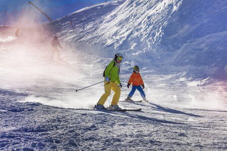 roofless: Mom and child ski down the piste teaching how to go down with sunlight lit through snow mist Stock Photo