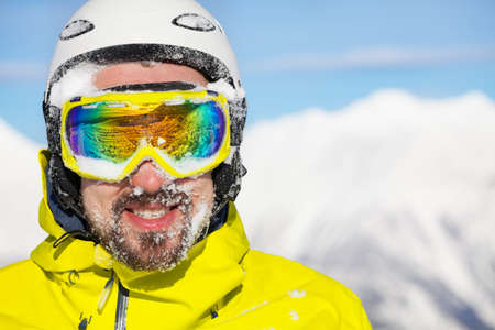 ski mask: Close portrait of a man wearing beard ski mask and helmet with snow on face and mountain on background