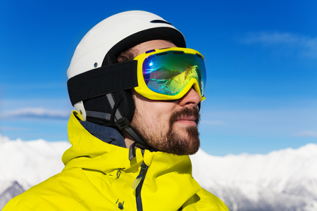 ski mask: Close profile portrait of a man with beard wearing ski mask and helmet over mountains