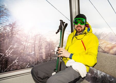 ski mask: Man skier with beard and wearing ski mask sit in ski lift cable car cabin Stock Photo
