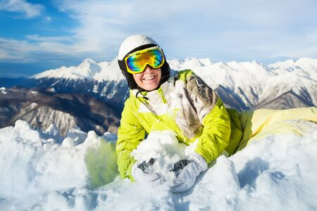 ski mask: Woman in ski mask and helmet lay in snow smiling and having fun wearing mask and helmet