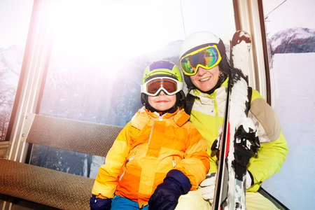 kids at the ski lift: Child and mother sit in cablecar lifting on top of the mountain with ski and smiling Stock Photo