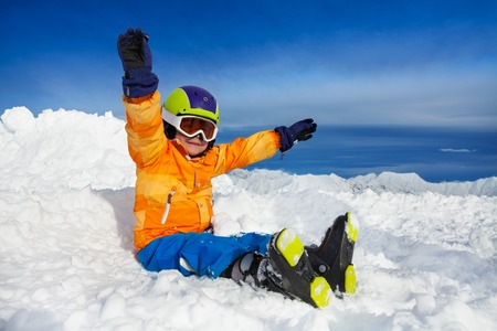 lifted hands: Little boy sit in snow wearing ski boots helmet and mask with lifted hands