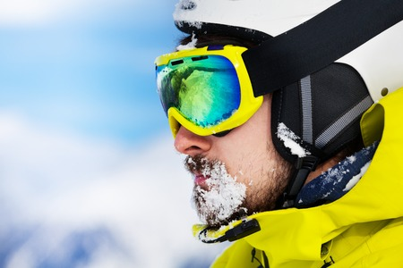 ski mask: Close portrait of a man with beard and ski mask and helmet with snow on beard