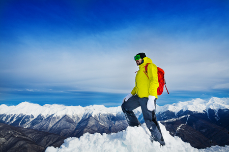 top mountain: Man hiker stand on top of the mountain peak covered with snow wearing backpack