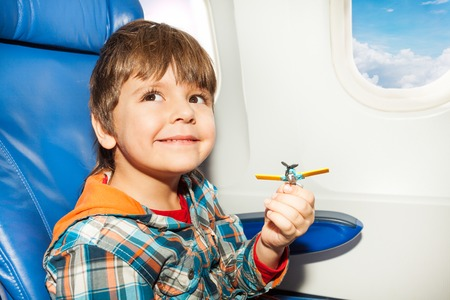 5 years: Little boy fly in airplane and playing with toy plastic plane looking at camera Stock Photo