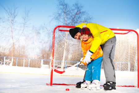 Father teach son to play ice hockey and hold hockey stick standing near gates on ice Archivio Fotografico