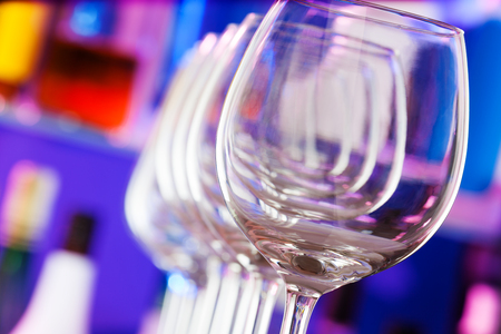 winy: Set of empty clean transparent wine glasses standing in a row close-up shoot Stock Photo