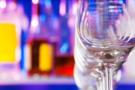 winy: Close-up photograph of a wine glasses standing in a row in bar with bottles on background