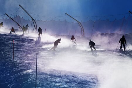 ski track: Silhouettes of skiers go down on ski track down with light go through snow mist