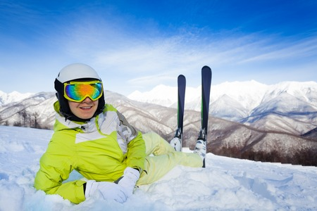 resting mask: Woman in mountain with ski helmet and mask lay in the snow turning back and resting Stock Photo
