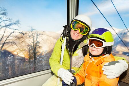 kids at the ski lift: Close portrait of mother and little boy son skier sit in cable car cabin on ski resort Stock Photo
