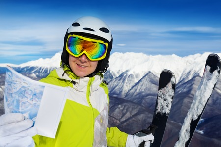 ski mask: Young woman stand with mountain ski mask and helmet holding map of ski resort tracks Stock Photo