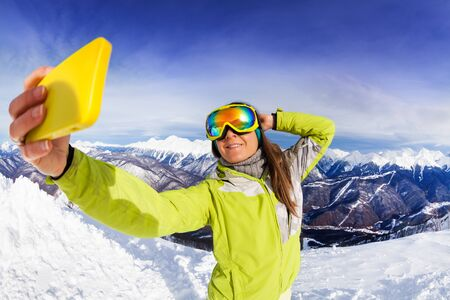ski mask: Woman on ski resort taking selfie photograph with phone wearing ski mask