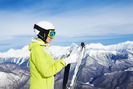 ski mask: Portrait of a woman looking in resort map wearing ski mask with mountain peaks on background Stock Photo