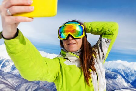 ski mask: Close portrait of a woman taking selfie with phone wearing ski mask with mountain peaks on background Stock Photo