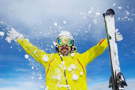 throw up: Man skier with beard throw snow up over blue sky wearing helmet and mask