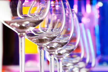 winy: Transparent wine glass in a row composition in a bar with transparent glass
