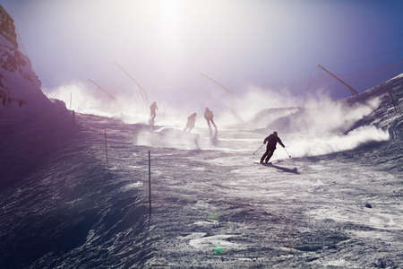 extreme sports: Many different skiers and snowboarders ski down the track with bright sun over snow