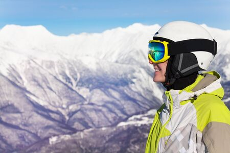 ski mask: Close profile portrait of a woman wearing ski mask and helmet over mountains