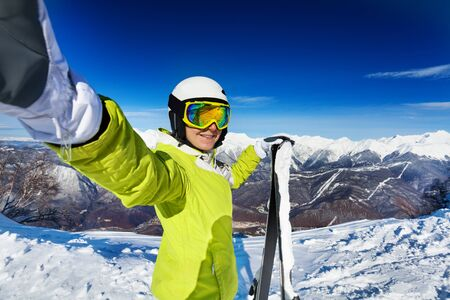 ski mask: Woman taking selfie with stretched hand wearing ski mask and helmet and holding ski in high mountain