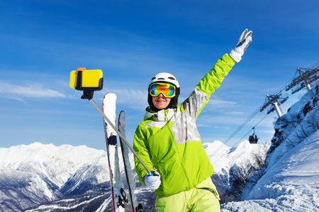 Vrouw die een selfie met stok neemt en opgeheven hand over de berg en kabelbaan skilift met hutten