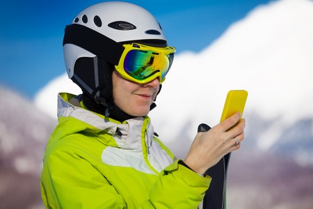 ski mask: Close portrait of a woman texting with phone wearing ski mask with mountain peaks on background