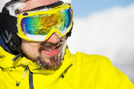 ski mask: Close-up portrait of a man wearing beard ski mask and helmet with snow on face and mountain on background
