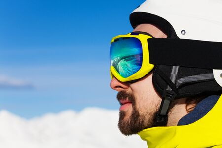 ski mask: Close-up profile portrait of a smiling man with beard wearing ski mask and helmet over mountains Stock Photo