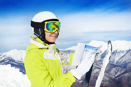ski mask: Mountain skier woman stand with map of pistes wearing helmet and ski mask Stock Photo
