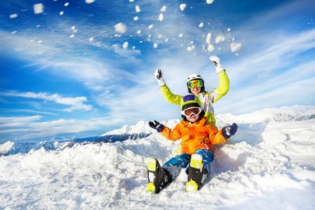 お母さんと子供スキー服マスクとヘルメットに座るし、雪を投げる 写真素材
