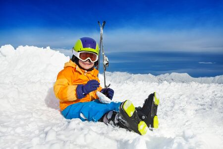 nice smile: Little boy with mountain ski clothes helmet and skies sit in snow and resting with nice smile