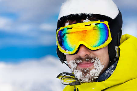 ski mask: Close portrait of skier man in ski mask and helmet with snow on beard Stock Photo