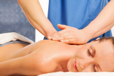 rubdown: Beautiful woman in a spa salon relaxing with massage therapy