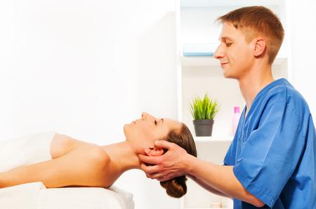 rubdown: Professional masseur doing head massage on woman in the spa salon