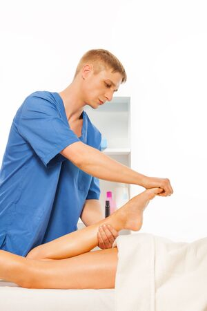 rubdown: Young masseur making feet massage in the light spa salon