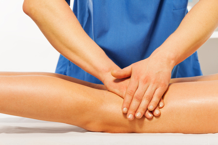 kneading: Close-up of masseurs hands kneading female leg in massage cabinet