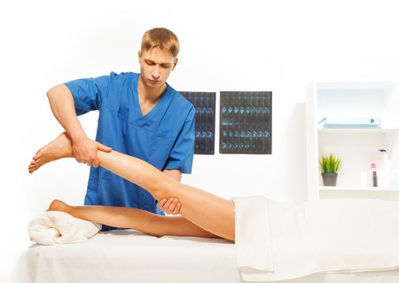rubdown: Masseur doing exercises with woman leg at massage room