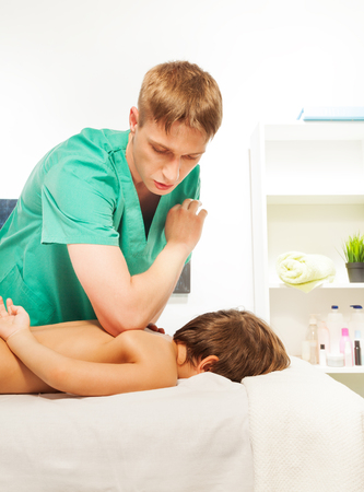 rubdown: Little boy rests with spa on the massage table at the massage cabinet