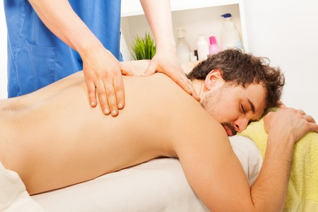 rubdown: Young man laying at the massage couch getting acupressure in the beauty salon