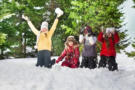 snow forest: Happy four kids, friends, standing on their knees at sunny winter day in the forest throwing snow