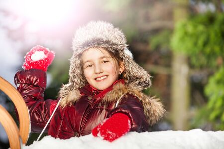 skids: Smiling girl having fun with snowball fight at the sunny winter day
