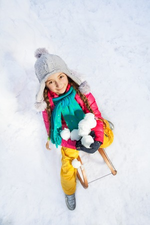 neve palle: Smiling girl sitting on sledge with snowballs at the white snow top view